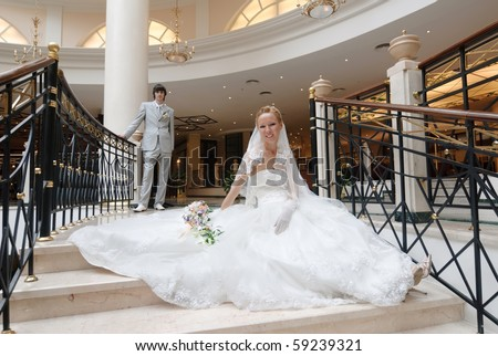 stock photo Bride in beautiful wedding dress sits on wide spiral staircase