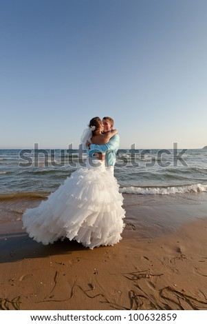 Bride in bridal dress and groom in white trousers and blue shirt kissing at the beach
