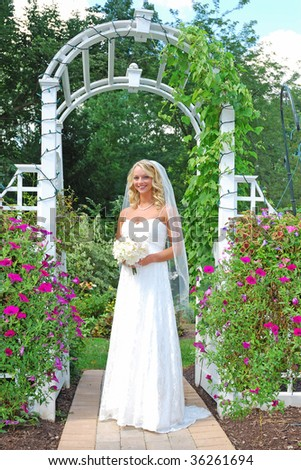 bride in front of the white arch in the rose garden