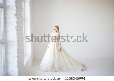 322949fe04d bride in her wedding dress look in window  1108345994 · blond bride in wedding  dress running and dancing in big white room ...