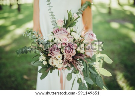 Bride in light white dress standing in woods and holds a bouquet of flowers and greenery