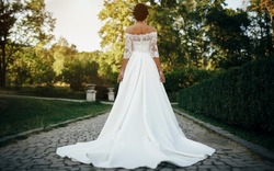 Bride in the park is a beautiful long wedding dress turned back