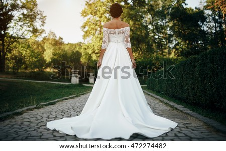 Bride in the park is a beautiful long wedding dress turned back Сток-фото ©