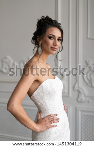 Bride in wedding dress and hairdo high beam posing in interior studio. Bride image with makeup and hairdo