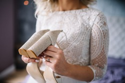 Bride in wedding dress hold her wedding shoes. Details.