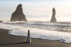 Bride in wedding dress silhouette at famous black volcanic Reynisfjara beach, Iceland
