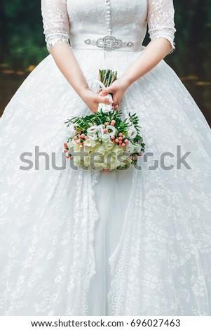 Bride in Wedding Dress with Wedding Bouquet in Hands