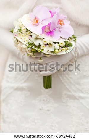 bride in white clothes holding beautiful wedding bouquet with orchids