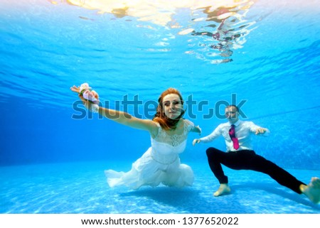 d8318beab0d4a Bride in white dress and groom swim and pose underwater on camera at the  bottom of