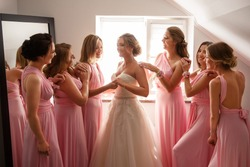 Bride in white wedding dress and bridesmaids in pink dresses posing in hotel or fitting room at wedding day.