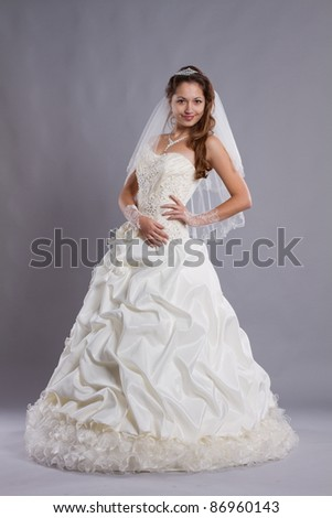 Bride in white wedding dress isolated on gray