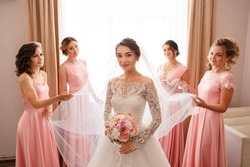 Bride in white wedding dress with long sleeves and bridesmaids in pink dress posing near window before wedding ceremony