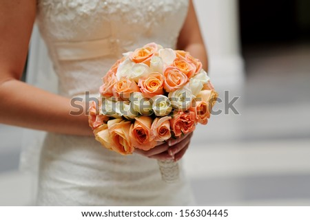 Bride is holding a bouquet in hand