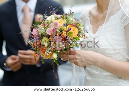 Bride is holding a wedding bouquet and a glass of champagne