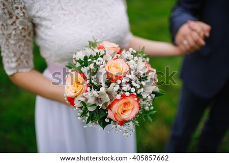 Bride is holding beautiful bright wedding bouquet