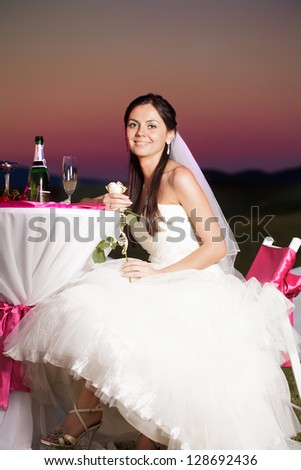 Bride is sitting at the wedding table outdoors with champagne and flower in the evening glow