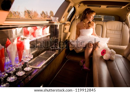 Bride is sitting in limousine and getting ready to get out
