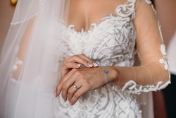 Bride jewls on hand, ready for wedding ceremony. White dress and caucasian skin.