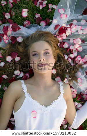Bride laying in grass and flower petals