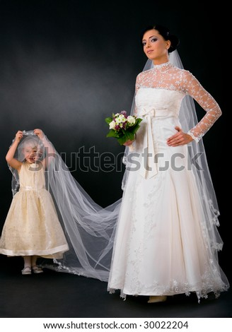 Bride posing in romantic white wedding dress, holding bouquet of flowers, little bridesmaid holding her veil.