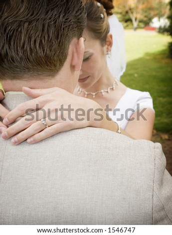 Bride puts arms around groom in the middle of the park