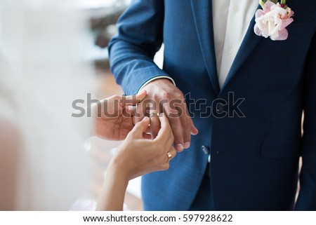 Bride puts ring on groom's finger #597928622