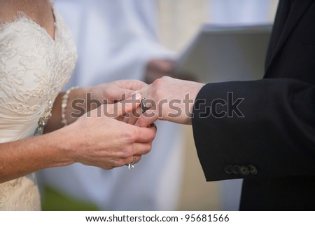 Bride putting a ring on groom's finger at wedding ceremony