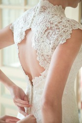 Bride putting on her white wedding dress. Wedding celebration concept. Beautiful lace wedding dress of the bride with open back