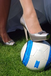 bride's foot in shoes on top of a soccer ball at football field