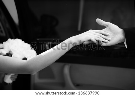 bride's hand and the hand of the groom while getting out of the car