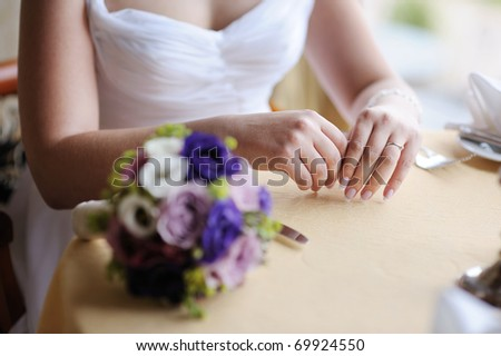Bride's hands and a wedding bouquet on a table