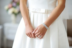 Bride's hands on beautiful white wedding dress. Bride wearing shiny bracelet.