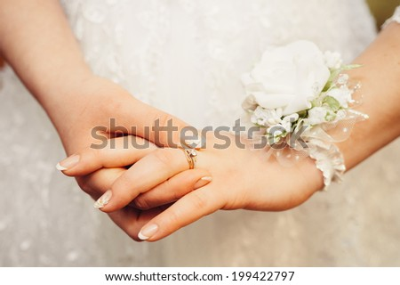 Bride\'s hands with ring over her wedding dress