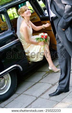 Bride sitting in wedding car with groom aside