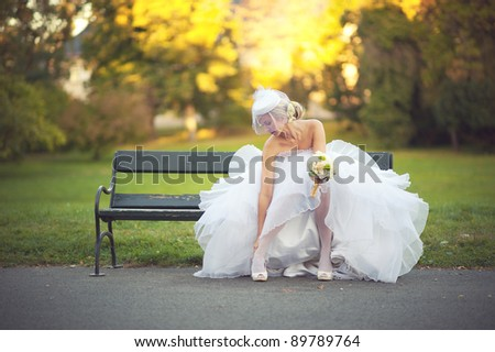 Bride sitting on a bench in a park