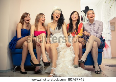 Bride sitting with girlfriends in professional fashion designer studio