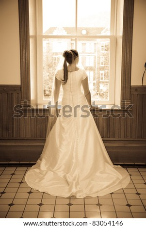 Bride standing at a window looking out