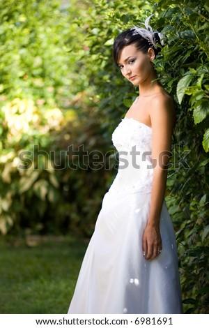 bride standing in garden in white gown