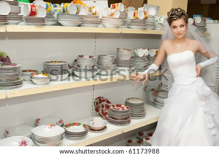 bride standing next to shelves with dishes and plates in kitchen utensils section of a store