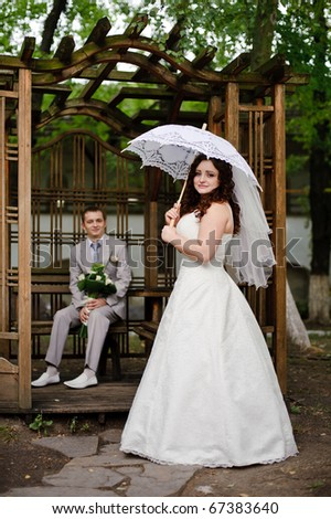 bride stands with summer umbrella, the groom sits in the gazebo