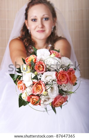 bride stretches a beautiful bouquet of orange and white roses