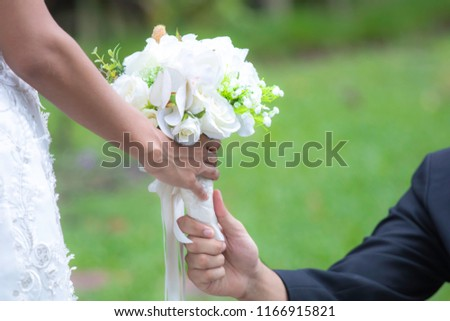 Bride take the beautiful flower bouquet from her groom in the park on her wedding ceremony day/ wedding couple concept #1166915821