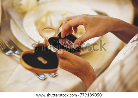 Bride takes a coin with a keyhole from a chest in form of the heart #779189050