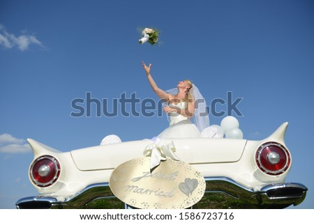 Bride Throwing Bouquet From Open Top Car On Wedding Day