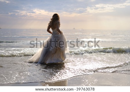Bride walking along sea coast in the wedding dress
