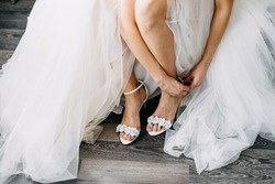 Bride wearing a wedding dress, putting on her shoes in the morning.