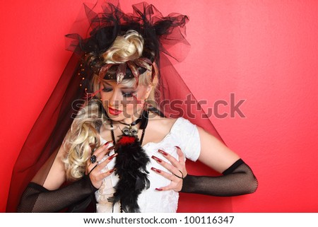 bride wearing black net gloves and unusual hat with black veil clings to breast on red background