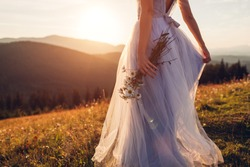 Bride wearing blue wedding dress holding bouquet in mountains at sunset. Woman walking on meadow in flowers