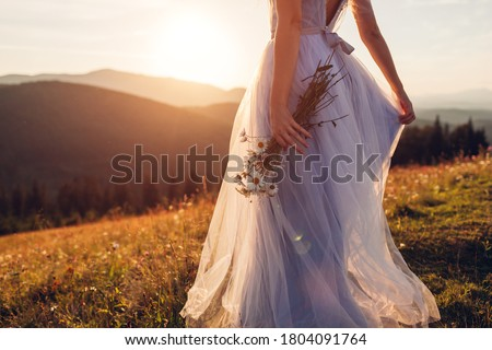 Bride wearing blue wedding dress holding bouquet in mountains at sunset. Woman walking on meadow in flowers Foto stock ©