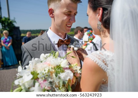 bride wearing buttonhole on a jacket of young and handsome groom